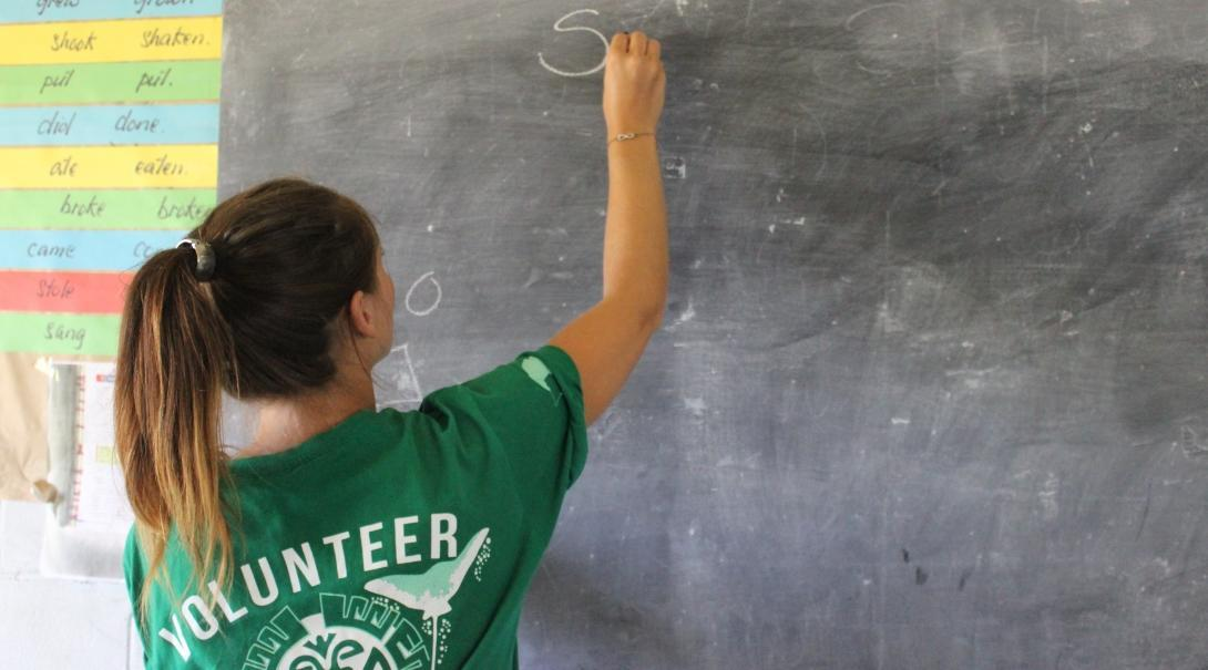 A volunteer teaching in Samoa writes on a classroom board.